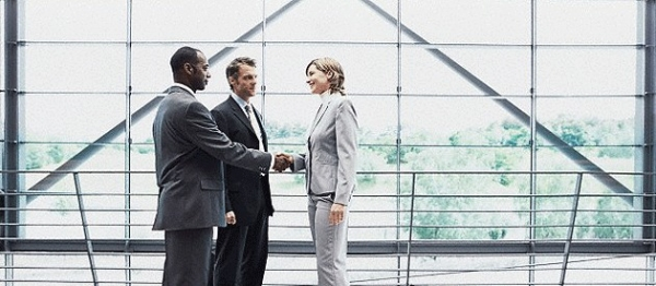 Executive Woman Greeting Two Businessmen